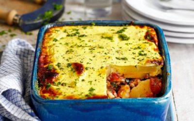 Vegetar moussaka med ost serveret i fad.